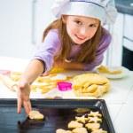 Little girl puts on baking cookies — Stock Photo #38472369