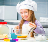 Cute little girl in the kitchen preparing cookies — Stock Photo