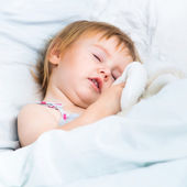 Baby with a toys in white bed — Stock Photo
