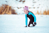 Cute little girl on the ice in — Stock Photo