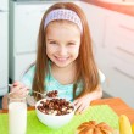 klein meisje haar ontbijt eten — Stockfoto #41776111