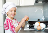 Girl cracking an egg — Stock Photo
