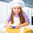 Cute little girl in the kitchen preparing cookies — Stock Photo #41976199