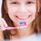 Little girl brushing teeth in bath — Stock Photo
