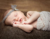 Pretty  newborn girl sleeping on a cot — Stock Photo