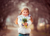 Little girl with a snowdrops — Stock fotografie