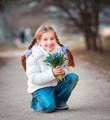 Little girl with a snowdrops — Stockfoto