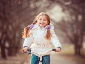 Little girl on a bicycle — Stok fotoğraf