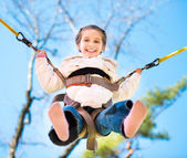 Little happy  girl jumping on the trampoline — Stock Photo