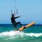 Young handsome Kite Surfer in sea waves — Stock Photo