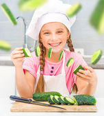 Girl cuts cucumbers in kitchen — Stock Photo