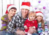 Happy family in Santa caps — Stock Photo