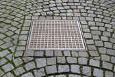 Paving stones with metal manhole — Stock Photo