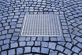 Paving stones with metal manhole — Stok fotoğraf