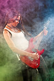 Fashion girl with guitar playing hard-rock. Coloured fog and lig — Stock Photo