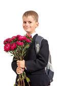 Skolpojke håller blommor. tillbaka till skolan — Stockfoto