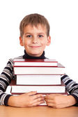 Schoolboy and a heap of books isolated on a white background — Stock Photo