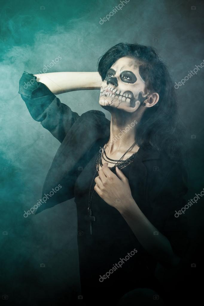 Young woman in day of the dead mask skull face art. Halloween face art with fog on black background   Stock Photo #13303388