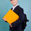 Cute schoolboy is holding an orange book - Stock Photo