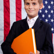 Cute schoolboy is holding a book against USA flag - Foto de Stock