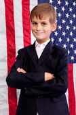 Portait of Caucasian boy with American flag in background. — Stock Photo