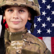 Boy USA soldier in front of American flag. — Stock Photo