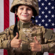 Boy USA soldier is showing thumbs up in front of American flag. — Stock Photo