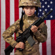 Royalty-Free Stock Photo: Boy USA soldier in front of American flag with rifle