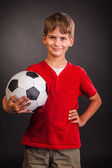Cute boy is holding a football ball. Soccer ball — Stock Photo