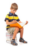 Schoolboy is sitting on books. Back to school — Stock Photo