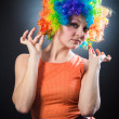 Woman in clown's wig smiling pulling fake hair on the sides — Stock Photo #24399245
