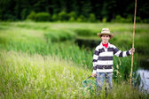 Young boy fishing in a river — Stock Photo