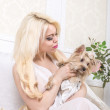 Luxurious blonde woman in a white dress with a dog pekingese — Stock Photo