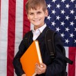 Cute schoolboy is holding a book against USA flag — Foto de Stock