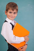Cute schoolboy is holding an orange book — Stock Photo