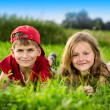 Cut boy and a girl are resting on the green grass in summer — Stock Photo #28714317