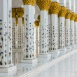 Hallway with golden decorated pillars at the entrance of the world famous landmark Sultan Sheikh Zayed Mosque in Abu Dhabi, UAE — Stock Photo