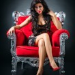 Young woman in a red chair — Stockfoto