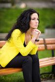 Beautiful sad girl sitting on the bench — Stock Photo
