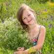 The little girl is stanging in the grass and holding a bouquet — Stock Photo