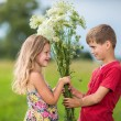 Spring. Boy gives girl a bouquet of flowers . — Stock Photo