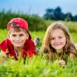 Cut boy and a girl are resting on the green grass in summer — Foto Stock