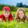 Cut boy and a girl are resting on the green grass in summer — Stock fotografie