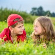 Cut boy and a girl are resting on the green grass in summer — Stock Photo #36536243