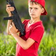 Boy holding a gun in the field. — Stock Photo