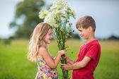 Spring. Boy gives girl a bouquet of flowers . — Foto Stock