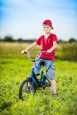 Jonge jongen fietsten in een park — Stockfoto