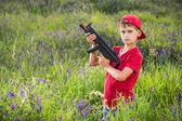 Boy holding a gun in the field. — Stockfoto
