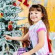 Little girl is decorating christmas tree — Stock Photo #37097049