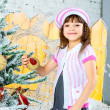 Stock Photo: Little girl is decorating christmas tree